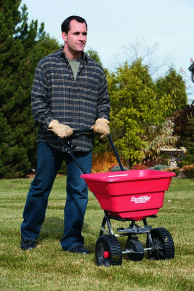 a photo of a man with fertilizer spreader