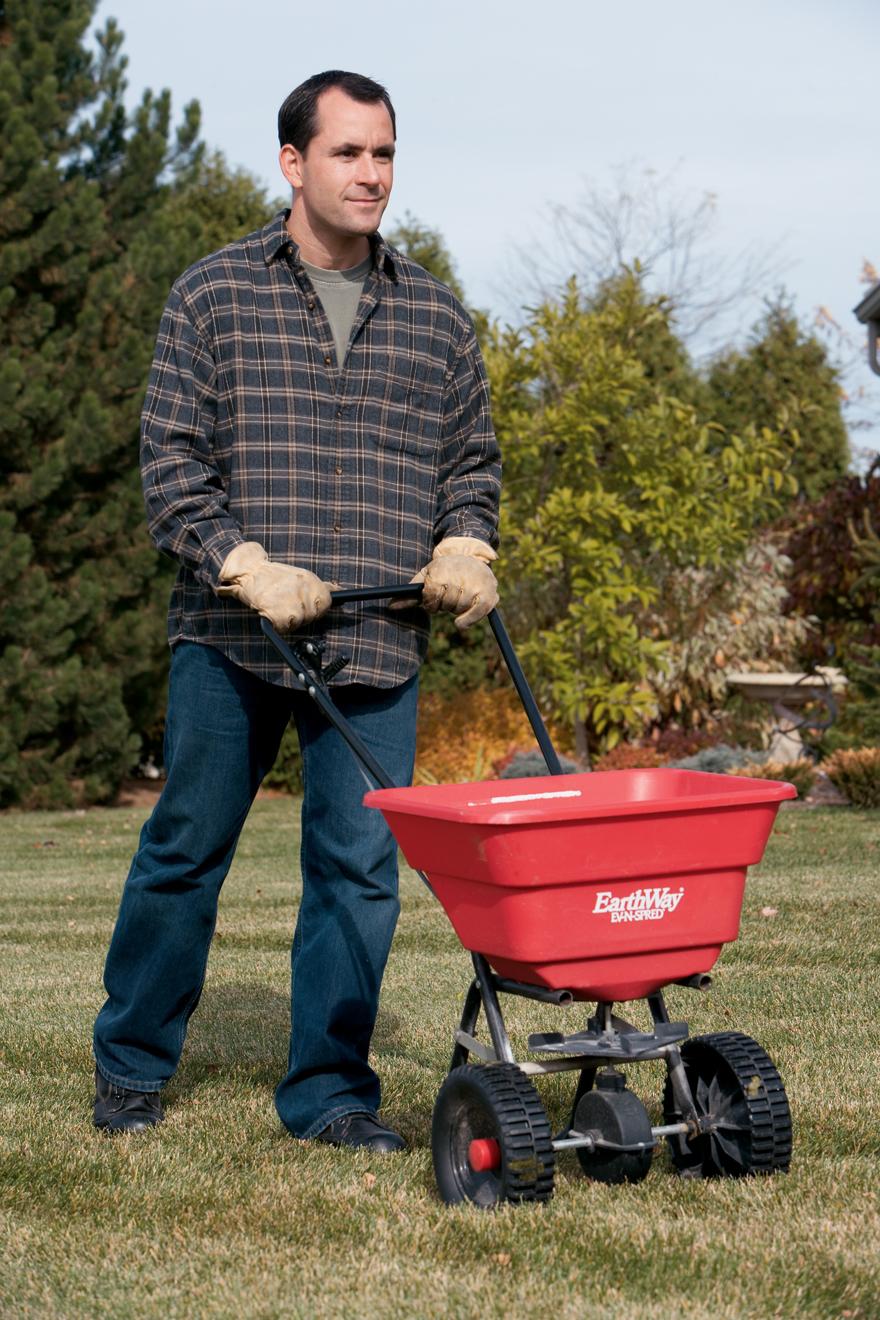 a photo of a man fertilizing a lawn