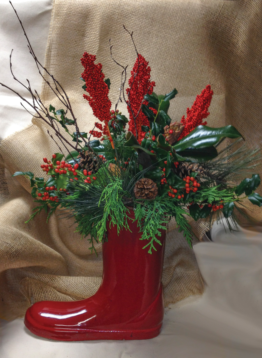 A photo of a red book with evergreens and other floral decorations.