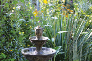 An image of a fountain in a native wildflower garden